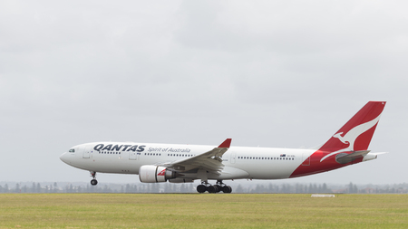 commits: Sydney - February 26, 2016: Large passenger plane Airbus A330-203 Qantas Airways with kangaroo painted on the tail, landing at the airport in Sydney February 26, 2016, Sydney, Australia