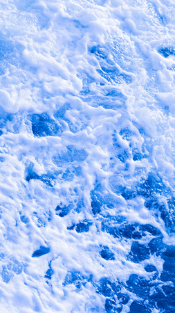 bubbling: beautiful clear blue sea water flowing bubbling white foam and splashing wave splashing splashes and drops vertically