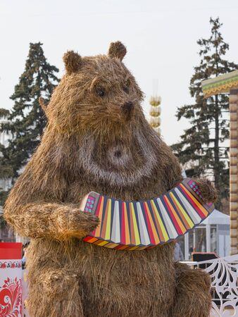 enea: Moscow - March 11, 2016: Bright festive Mardi Gras and straw stuffed bear at the fair ENEA 11 March 2016, Moscow, Russia Editorial