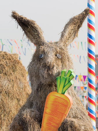 enea: Moscow - March 11, 2016: Bright festive Mardi Gras and a stuffed rabbit on the straw ENEA Fair March 11, 2016, Moscow, Russia