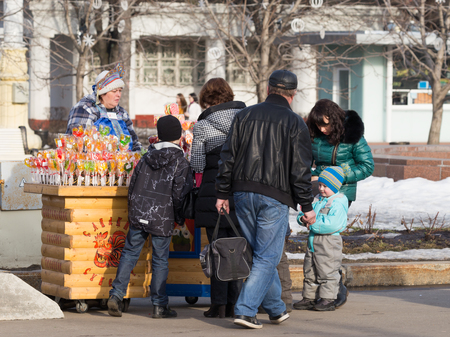 enea: Moscow - March 11, 2016: Bright cheerful festive Mardi Gras and people buy cofete - ledintsy at ENEA Fair March 11, 2016, Moscow, Russia