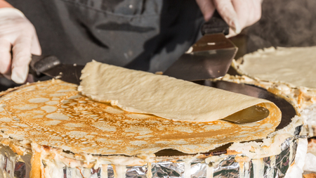 uneven edge: Chef hands with rubber gloves overturned delicious appetizing ruddy browned on one side of the pancake, using a special metal blade during Shrovetide