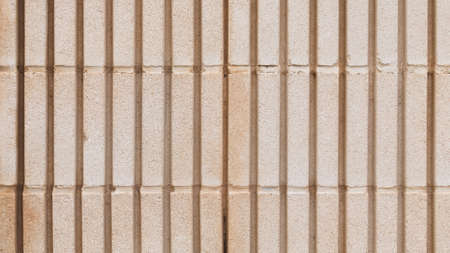 under the influence: surface of an old wall of beige colored shaped concrete blocks, with coarse seams and joints, with vertical stripes, outdoors Stock Photo