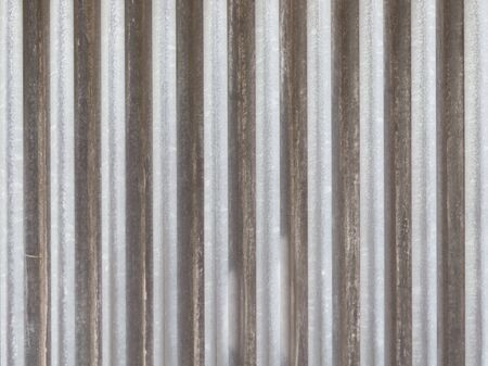 under the influence: surface of old gray dirty profiled aluminum fence with vertical stripes on the street