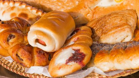 uneven edge: delicious tasty pie with sausage and sweet blush buns and cakes with jam on straw plate - a traditional Russian style