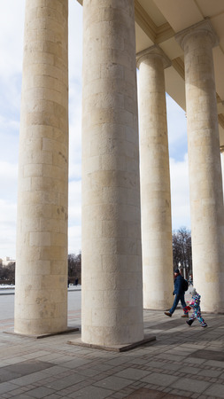 named: Moscow - March 13, 2016: Central entrance to the Park of Culture and Rest named after Gorky, a colonnade, and the father and son come to the park March 13, 2016, Moscow, Russia Editorial