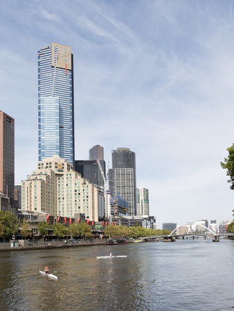 tallest bridge: Melbourne - March 7, 2016: Two men in a canoe floating down the river on a background of the Yarra skyscraper Eureka and pedestrian bridge in good weather in the summer of March 7, 2016, Melbourne, Australia