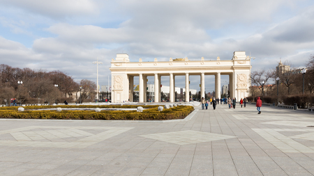 named: Moscow - March 13, 2016: Central entrance to the Park of Culture and Rest named after Gorky, a colonnade, and a lot of people go for a walk in the park March 13, 2016, Moscow, Russia Editorial