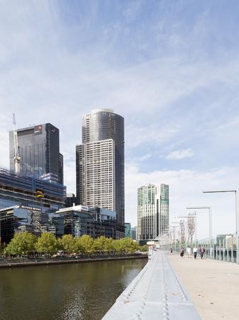 pedestrian bridge: Melbourne - February 23, 2016: Beautiful cityscape, skyscraper Eureka gold and pedestrian bridge over a large river Yarra February 23, 2016, Melbourne, Australia