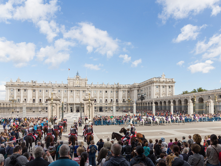 Madrid - 7 October 2015: Changing of the guard at the Royal Palace and the riders on beautiful horses galloping over the area and a lot of people around October 7, 2015, Madrid, Spain