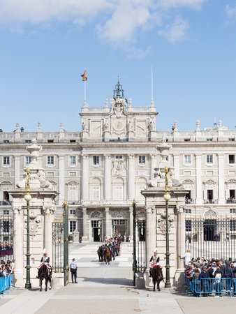 Madrid - 7 October 2015: Changing of the guard at the Royal Palace and the riders on beautiful horses galloping over the area and a lot of people around, vertically October 7, 2015, Madrid, Spain