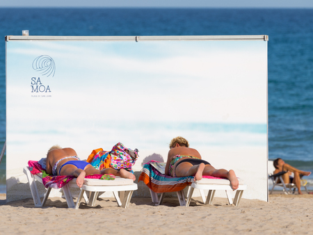 bathing suits: Alicante -12 October 2015: Two women with colorful towels and bathing suits sunbathing on a sun lounger, hiding from the blue sea behind the white wall on the beach October 12, 2015, Alicante, Spain Editorial