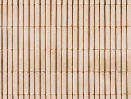 unfavorable: large surface of an old wall of beige colored shaped concrete blocks, with coarse seams and joints, with vertical stripes, outdoors
