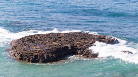 unusually: big brown stone - an island in the sea, the birds sit on it, and the waves breaking on the rock and the water from the blue turns green