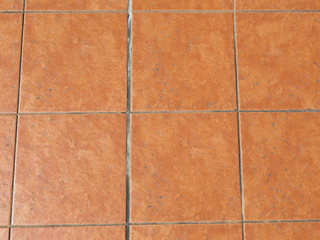 uneven edge: old ceramic terracotta square paving slabs with old gray seams Stock Photo