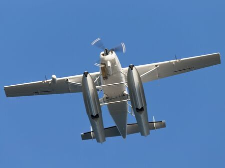 unmarked: White light-engine floatplane with a rotating propeller unmarked flying against a bright blue sky