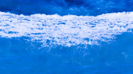 bubbling: clear turquoise blue sea wave flowing bubbling and splashing, forming a beautiful white foam