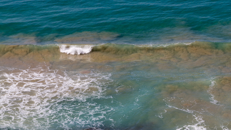 bubbling: beautiful clear blue turquoise sea wave flowing bubbling and splashing, forming white foam, and lifting up brown sand from the bottom of Stock Photo