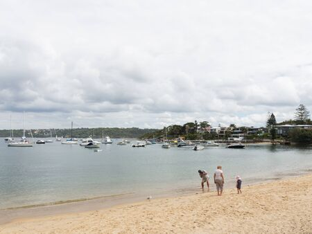 personas tomando agua: Sydney - March 1, 2016: Sydney beach and people walk with the child, and taking pictures from sea water Sydney Harbour March 1, 2016, Sydney, Australia