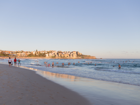 lowrise: Sydney - March 1, 2016: Beautiful city beach and people swimming at sunset and yellow sunlight on urban low-rise building March 1, 2016, Sydney, Australia