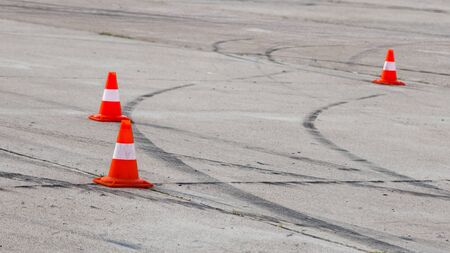 racetrack: Black traces of protectors on the gray pavement and bright red traffic cones on the racetrack
