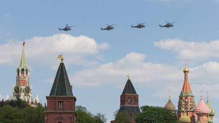 spassky: Moscow - May 7, 2016: Military helicopters during the final rehearsal of the Victory parade fly over Red Square at the Spassky Tower and St Basils Cathedral May 7, 2016, Moscow, Russia