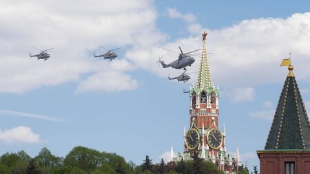 may fly: Moscow - May 7, 2016: Military helicopters during the final rehearsal of the Victory parade fly over Red Square Spasskaya tower at May 7, 2016, Moscow, Russia Editorial