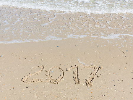 small stones: 2017 inscription on a light yellow sand fines with small stones and fragments of shells on the sandy beach and a wave of clean sea water with white foam Stock Photo