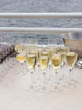 poured: Sparkling champagne poured into glass transparent tall wine glasses at corporate parties on the cruise boat and the sea in the background