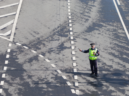 Moscow - May 9, 2016: A man - a policeman in a police uniform, regulates traffic on a background of a wet asphalt road with white road markings May 9, 2016, Moscow, Russia