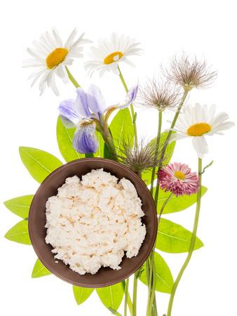 fleurs des champs: frais délicieux fromage blanc fait maison dans un bol d'argile brune sur un fond de feuilles vert clair sous la forme d'une fleur et délicates fleurs sauvages, isolé sur fond blanc