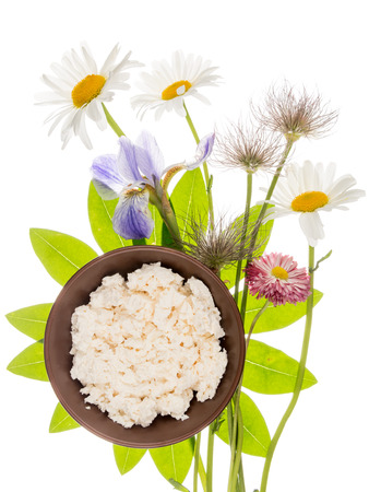 wildflowers: fresh delicious homemade white cheese in brown clay bowl on a background of bright green leaves in the shape of a flower and delicate wildflowers, isolated on white background