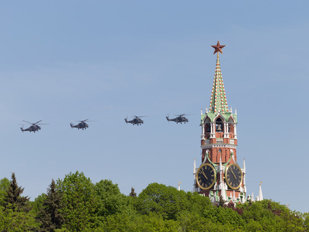 rotates: Moscow - May 9, 2016: Four gray military helicopters Mi-35 flying on the background of the Spasskaya Tower of the Kremlin, during Victory Day parade May 9, 2016, Moscow, Russia Editorial
