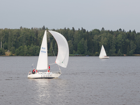 klyazma: Moscow region - 9 June 2015: Team of people sailing on a small sailing boat and the wind blowing in the white sail, summer Pestovo Reservoir June 9, 2015, Moscow Region, Russia Editorial