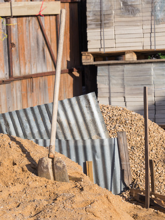 unskilled: The old iron shovel with a wooden handle lies on a pile of yellow sand, interspersed with gravel on a construction site against the backdrop of gofrolist, gravel pile, concrete tiles and wooden fence