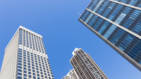 blue facades sky: beautiful geometric horizontal architectural abstraction of gray concrete and glass facades of high-rise buildings against the blue clear sky Stock Photo