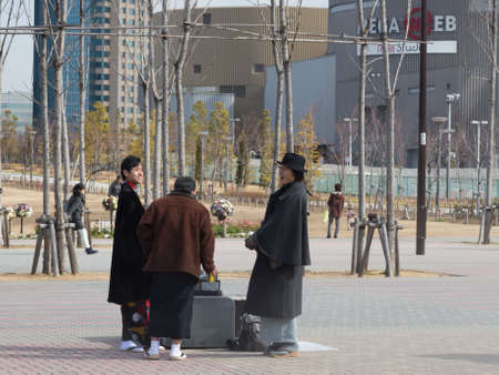 good weather: Tokyo - 7 February 2015: Unusually happy people dressed in the pedestrian area of Odaiba, in good weather 7 February, Tokyo, Japan