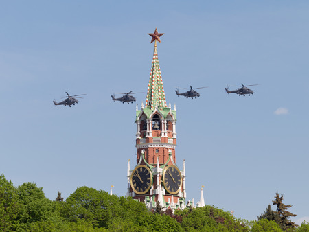 Moscow - May 9, 2016: Four gray powerful military helicopters Mi-35 flying on the background of the Spasskaya Tower of the Kremlin, during Victory Day parade May 9, 2016, Moscow, Russia Editorial