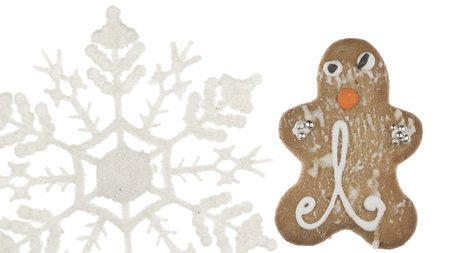 merry Christmas gingerbread man decorated with a pattern of sweet sugar fondant sugar and silver balls and white snowflake on a beautiful white background isolated