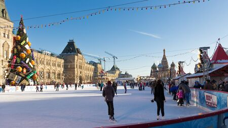 iceskating: Moscow - November 29, 2015: Big Christmas ice rink on Red Square and a lot of people are skating during the Christmas holidays, and St. Basils Cathedral November 29, 2016, Moscow, Russia Editorial