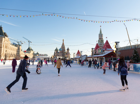 spassky: Moscow - November 29, 2015: Beautiful Christmas ice rink on Red Square and a lot of people are skating during the Christmas holidays and unusual St. Basil November 29, 2016, Moscow, Russia