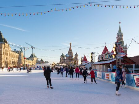 spassky: Moscow - November 29, 2015: Beautiful Christmas ice rink on Red Square and a lot of people are skating during the Christmas holidays and amazing St. Basil November 29, 2016, Moscow, Russia