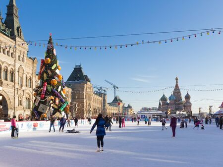 iceskating: Moscow - November 29, 2015: Beautiful Christmas ice rink on Red Square and a lot of people are skating during the Christmas holidays, and St. Basils Cathedral November 29, 2016, Moscow, Russia