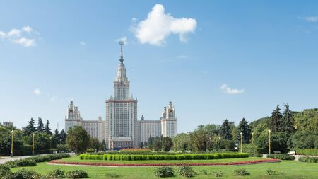 baccalaureate: Moscow - August 11, 2016: Beautiful Moscow State University named after Lomonosov on the Sparrow Hills and beautiful red flowers in the foreground, August 11, 2016, Moscow, Russia