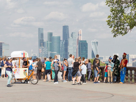 take a history: Moscow - August 11, 2016: View from the observation deck on the Sparrow Hills to unusual skyscrapers of Moscow City and a lot of tourists August 11, 2016, Moscow, Russia