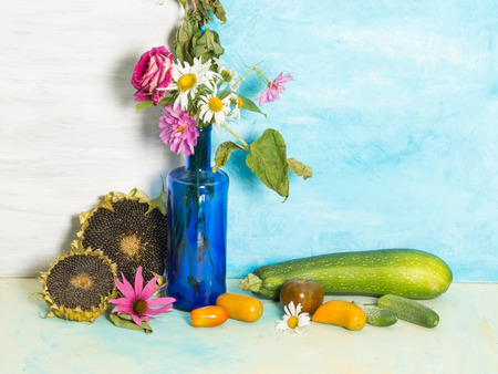 a rustic still life with sunflowers and ripe autumn vegetables and a bouquet of garden flowers in a blue glass bottle on a background of blue and white painted wall
