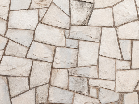 smudges: decorative light gray old rough wall made of natural sandstone with potholes and smudges on the street