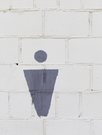 truncated: gray female symbol on the old brick, painted with white paint, wall, outside the urban toilet Stock Photo