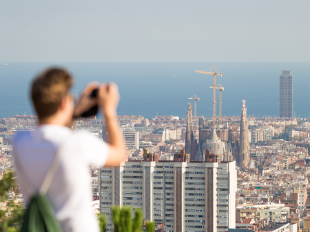 sagrada: Barcelona - 9 October 2015: unrecognizable tourist photographs the Catholic Cathedral of the Sagrada Familia and the blue sea in the distance, a top view of 9 October 2015, Barcelona, ​​Spain