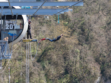 Sochi - April 4, 2017: A very brave man with a special rubber rope, jumping from the worlds longest pedestrian bridge in the Akhshtyr gorge April 4, 2017, Sochi, Russia Editöryel